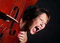 Girl face screaming by double bass Stock Photography