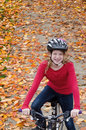 Girl on fall bike path looking down at a happy ten year old with braces sitting her a in the Royalty Free Stock Photography