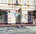 Girl falling off her bicycle on city street creative concept Stock Photography
