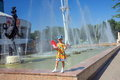 Girl with a fan walks near the fountains in almaty near the circus Royalty Free Stock Images