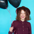 Girl in fashion clothes holding colored black balloons Royalty Free Stock Photo