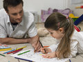 Girl And Father Coloring Book Together On Floor