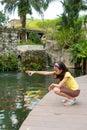 Girl feeding the exotic Koi carps Royalty Free Stock Photography