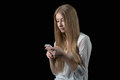 Girl feels depressed after reading bad sms on her mobile phone attractive young cellular isolated black Stock Image