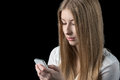 Girl feels depressed after reading bad sms on her mobile phone attractive young news cellular isolated black Royalty Free Stock Image