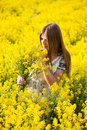 Girl in the field of yellow flowers with a bouquet Stock Images