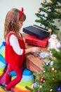 Girl in fine red dress opening gifts near Christmas tree Royalty Free Stock Photo