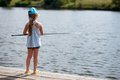 Girl fishing from a dock on a lake or pond. Royalty Free Stock Photo