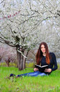 The girl in the flowered garden reading book a sit on grass Royalty Free Stock Images