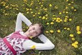 Girl in the flowering meadow on her back with planty taraxacum officinale dandelion Stock Photos