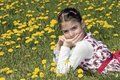 Girl in the flowering meadow looking at camera with planty taraxacum officinale dandelion Royalty Free Stock Images