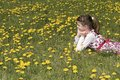 Girl in the flowering meadow looking far with planty taraxacum officinale dandelion Royalty Free Stock Image