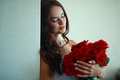 Girl with flowers pretty dark hair a bouquet of red roses Royalty Free Stock Images