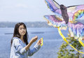 Girl flying kite by the lake Stock Image
