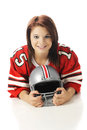 Girl with a football helmet close up image of beautiful teen in an oversized jersey and holding on white background Stock Images