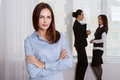 Girl in formal clothes is standing in the foreground and her colleagues have a talking background Stock Photography