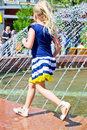 Girl at the fountain running around on a clear sunny day Royalty Free Stock Photos