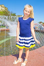 Girl at the fountain standing on a clear sunny day Stock Photography