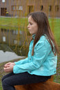 Girl with freckles cute teenager sitting outside at a little lake Royalty Free Stock Image