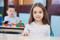 Girl with friend in background at preschool portrait of cute little Stock Image