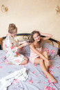 Girl friends blond attractive young women sitting portrait of in bed in pajamas one doing other braid pigtail Royalty Free Stock Photo