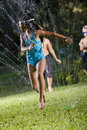 Girl with friends playing in lawn sprinkler Royalty Free Stock Photos