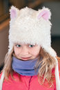 Girl in fun white artificial fur hat little blond closeup outdoor portrait Royalty Free Stock Images
