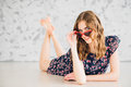 Girl in funny glasses on a floor Royalty Free Stock Photo