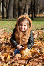 Girl in a fur jacket sits on the fallen down autumn leaves Royalty Free Stock Photos