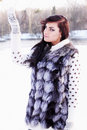 Girl in a fur vest catches snow young beautiful Royalty Free Stock Photos