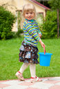 The girl in a garden with a toy bucket Royalty Free Stock Photo