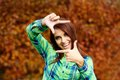 Girl with a gesture attractive smiling showing frame on background of yellow autumn foliage Stock Image