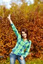 Girl with a gesture attractive smiling showing victory on background of yellow autumn foliage Royalty Free Stock Photo