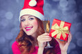 Girl with gift and champagne redhead in christmas hat Stock Images