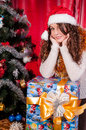 Girl with gifts near a Christmas tree Stock Image