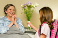 Girl giving bouquet of flowers to grandmother grandchild lying in bed Stock Photo