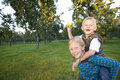 Girl (11-13) giving brother (9-11) piggy back, boy with apple, smiling, portrait Royalty Free Stock Photo