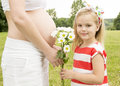 Girl giving flowers to mom beautiful gives a pregnant woman Stock Image