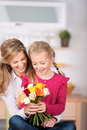 Girl giving flowers to mother on mother s day little her at home Stock Photo