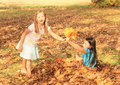 Girl giving maple leaves small kid smiling blond barefoot with long hair fallen into hand of other kid on autumn Stock Images