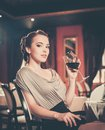 Girl with glass of red wine alone beautiful young in a restaurant Stock Photo