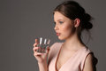 Girl with glass of water. Close up. Gray background Royalty Free Stock Photo