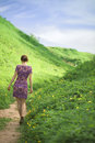 Girl goes on a footpath the between hills covered with fresh green grass bright sunny day of summer Stock Photography
