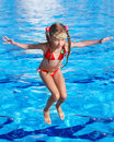 Girl with goggles and red swimsuit jump in pool. Royalty Free Stock Photo
