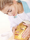 Girl with gold facial mask. Royalty Free Stock Image