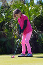 Girl golfer is putting on the green aims a ball Royalty Free Stock Photography