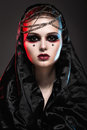 Girl in gothic art style with creative makeup black hood and chains Stock Photos