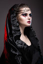 Girl in gothic art style with creative makeup black hood and chains Stock Image