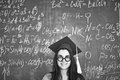 Girl in graduation hat black and white image of student and eyeglasses looking at camera on background of chalkboard Stock Image