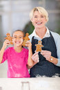Girl grandmother gingerbread happy little and holding just baked cookies in kitchen Stock Photo